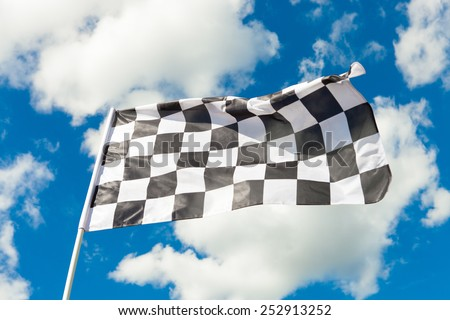 Checkered flag waving with blue sky and clouds behind it - stock photo