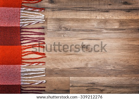 checkered plaid on wooden background - stock photo
