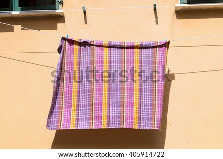 Checkered tablecloth hanging out the window to dry in Portovenere. Liguria, La Spezia - Italy - stock photo