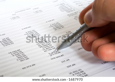 checking balance - man's hand holding pen and checking spreadsheet - stock photo
