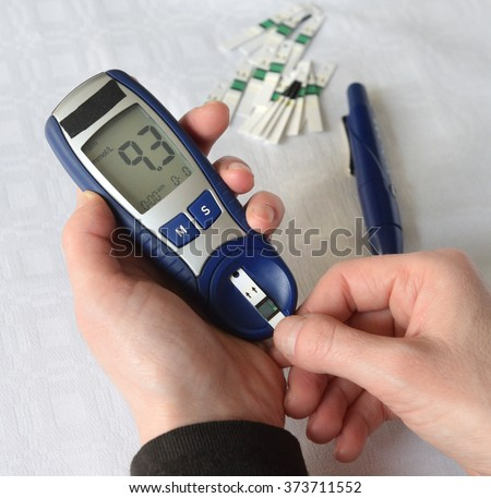 Checking blood glucose level with a glucose meter with blood drop