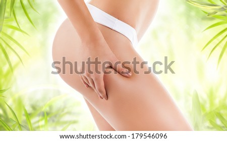 Checking cellulite, woman hip, close up of beautiful female body legs belly, perfect figure over green leaf background