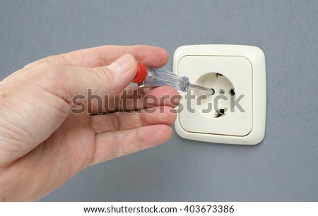 Checking if electrical wall outlet has voltage. - stock photo