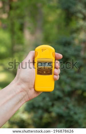 Checking radiation level with a personal dosimeter  (Ukrainian signs on the display says Work Settings: Gamma Dosage -> Real Time -> Alarm Clock) - stock photo