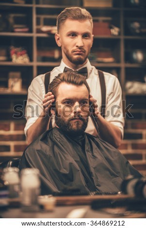 Checking symmetry. Hairdresser checking symmetry of haircut of his client at barbershop