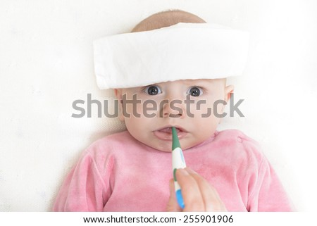 Checking temperature to a cute baby with a digital thermometer - stock photo
