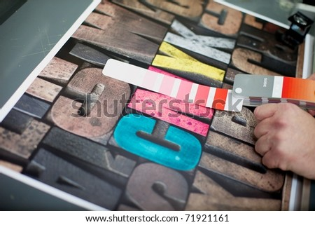 Checking the color match to a printed guide book - stock photo