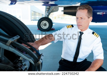 Checking the wheels. Confident male pilot in uniform examining an airplane wheels