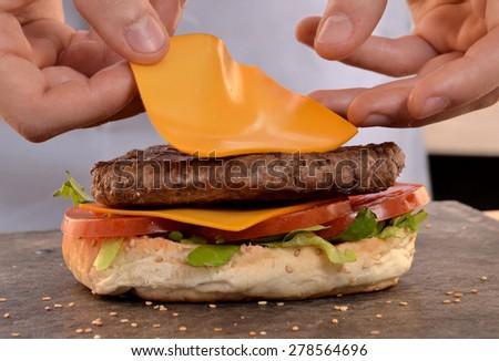 Cheddar cheese on burger.Preparing and making hamburger. - stock photo