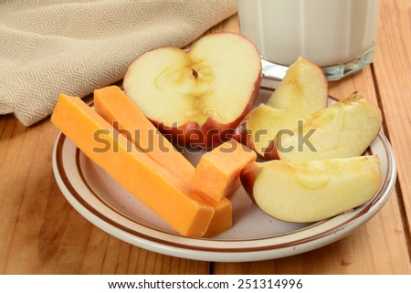 Cheddar cheese sticks with a sliced apple and milk - stock photo