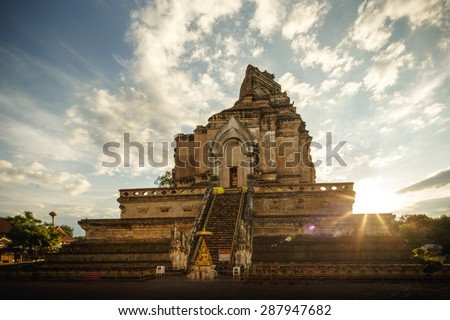 Chedi Luang Pagoda, Sunrise at Wat Chedi Luang Temple with cloudy sky and lens flare - Chiang mai, Thailand - stock photo