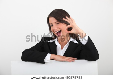 Cheeky young woman in a suit giving the OK sign with a blank board ready for text - stock photo