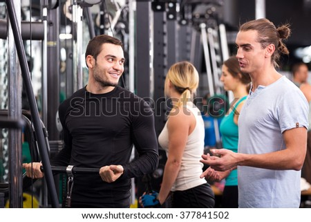 Cheerful active young people having weightlifting training in health club - stock photo