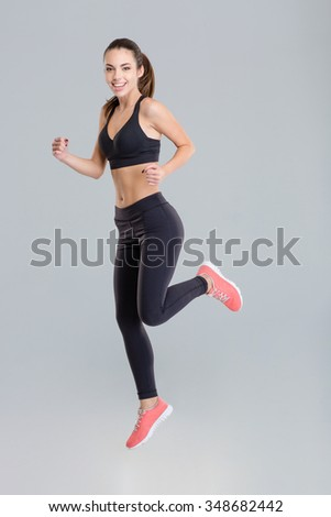 Cheerful active young sportswoman in fitness wear running isolated over grey background - stock photo