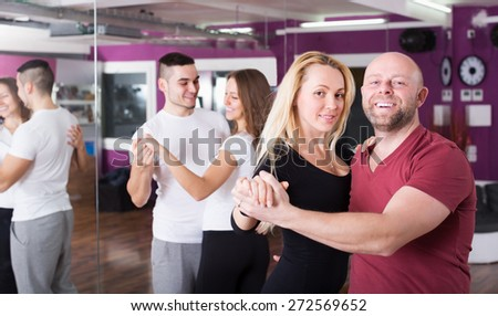 Cheerful adult couples enjoying of partner dance and smiling indoor - stock photo