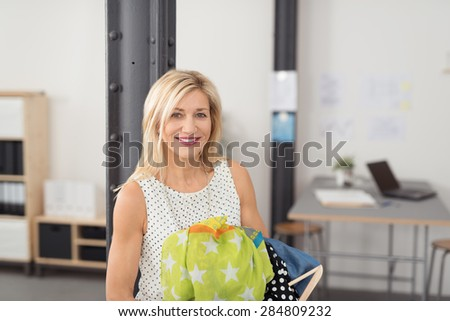 Cheerful Adult Office Woman with Blond Hair, Holding her Other Dresses While Smiling at the Camera. - stock photo