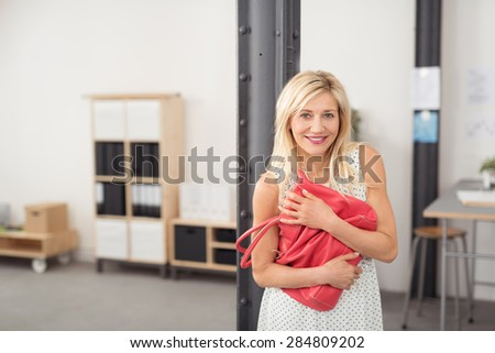 Cheerful Adult Woman with Blond Hair, Embracing her Pink Shoulder Bag Tightly While at the Office. - stock photo