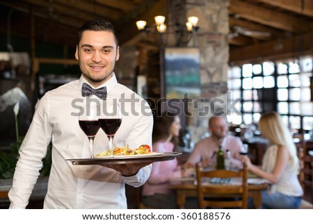 Cheerful adults people having dinner and respectful waiter - stock photo