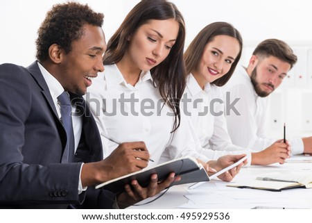 Cheerful African American businessman is making notes while sitting in his office and looking at his colleague's tablet computer. Concept of teamwork