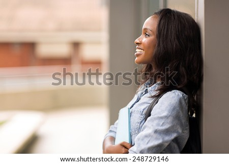cheerful african american college girl looking up - stock photo