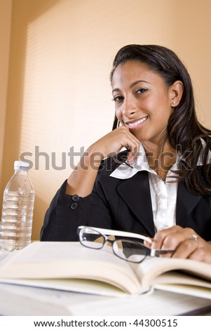Cheerful African-American university student studying a book - stock photo