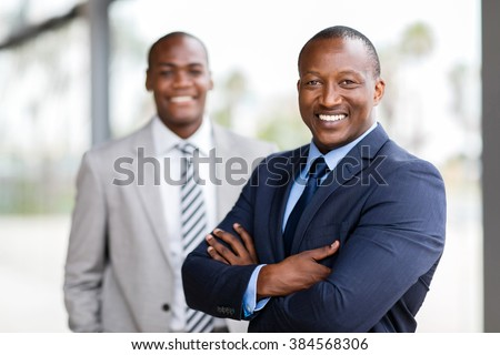 cheerful african businessman standing in front of colleague - stock photo