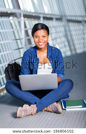 cheerful african college student using laptop - stock photo