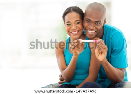 cheerful african couple showing positive pregnancy test - stock photo