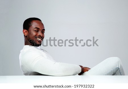 Cheerful african man sitting at the table on gray background - stock photo