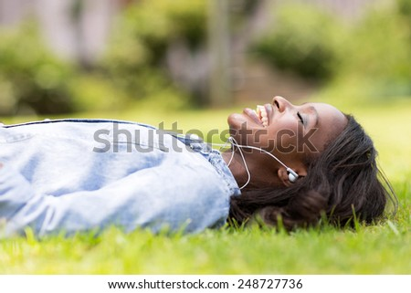cheerful african woman lying on grass listening to music outdoors - stock photo