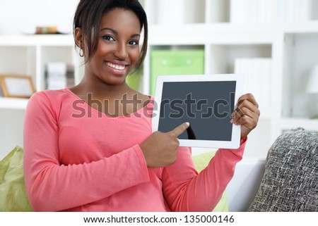 Cheerful African woman pointing at empty screen of  digital tablet