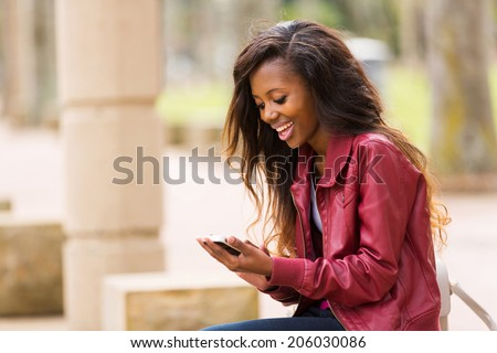 cheerful african woman using smart phone outdoors - stock photo