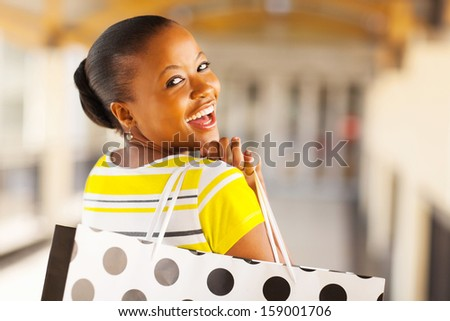 cheerful african young lady in shopping mall - stock photo