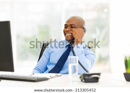 cheerful afro american businessman talking on landline phone in office - stock photo