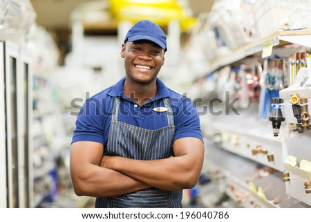 cheerful afro american hardware worker with arms crossed