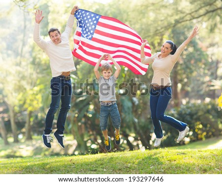 cheerful american family jumping with USA flag on 4th of july - stock photo