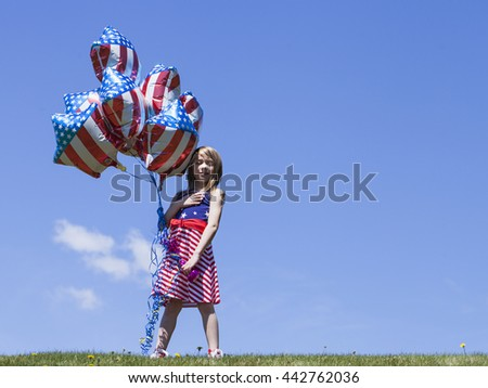 Cheerful American  girl holding balloons outside. 4th of July. Independence day.