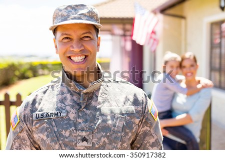 cheerful american military soldier standing in front of family - stock photo