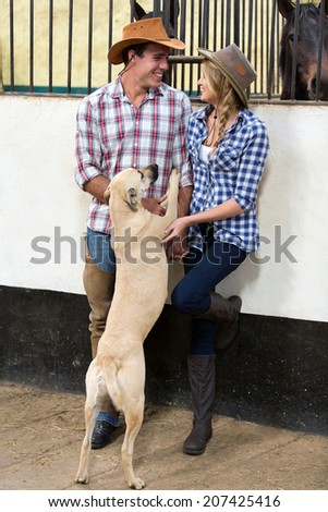cheerful american western couple playing with their dog inside stables - stock photo