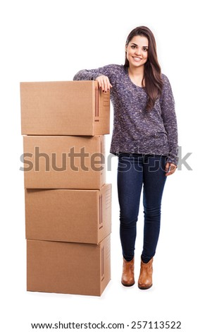 Cheerful and attractive young brunette leaning of a pile of boxes ready for shipping - stock photo