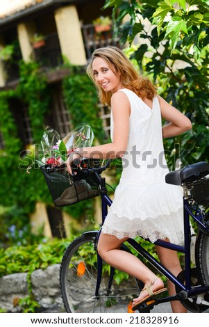 cheerful and attractive young woman riding bicycle during  summertime - stock photo