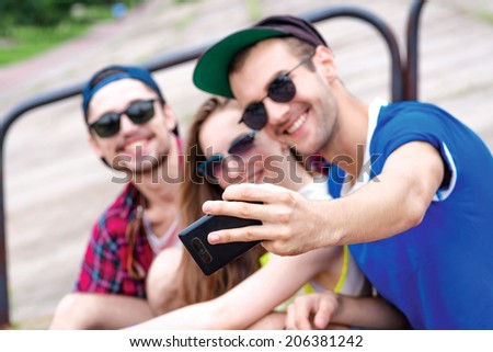 Cheerful and good day. Young friends have fun together on the street and smile at each other. Funny guys make Selfie - stock photo