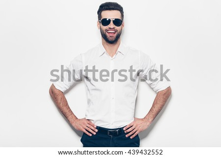 Cheerful and handsome. Handsome young man in white shirt holding hands on hip and looking at camera with smile while standing against white background  - stock photo