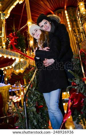 cheerful and happy young couple having fun in a merry-go-round in winter - stock photo
