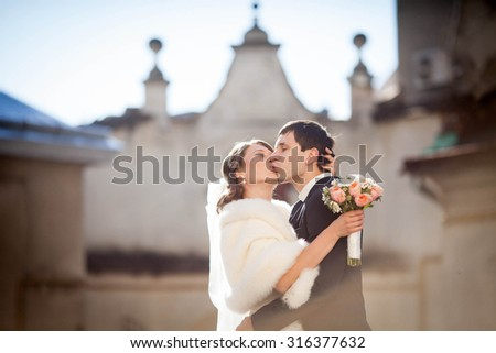 cheerful and smiling bride embrace on a background of church - stock photo