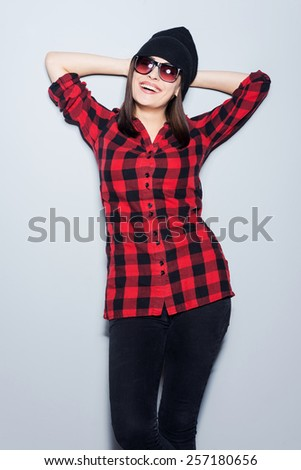 Cheerful and stylish. Attractive young woman in glasses posing and looking at camera while standing against grey background - stock photo