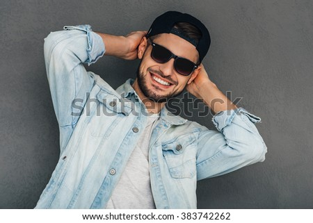Cheerful and trendy.Cheerful young man adjusting his baseball cap and looking at camerawith smile while standing against grey background