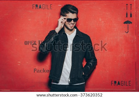 Cheerful and trendy look. Handsome young man adjusting his sunglasses and smiling while standing against red background - stock photo