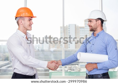 Cheerful architect and attractive foreman are shaking hands. The new plan was approved. They are smiling and looking at each other happily - stock photo