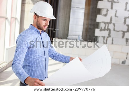 Cheerful architect is holding a blueprint.  He is looking at the sketches of construction with concentration. The man has a white helmet on his head - stock photo